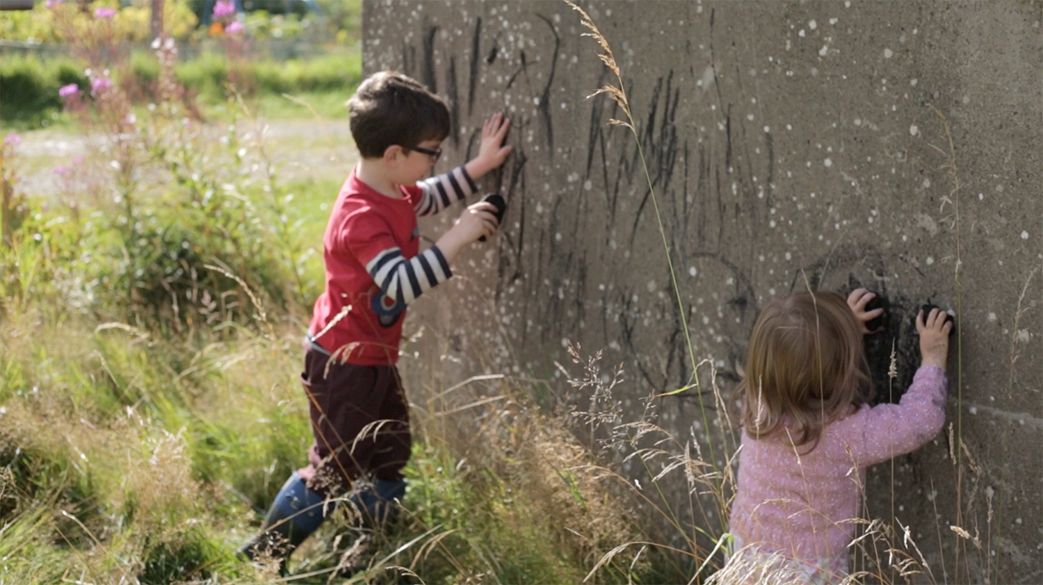 If play is neither inside nor outside where is it?, video still, children drawing on concrete wall